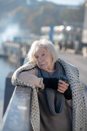 Having no food. Poor homeless woman having no food but drinking hot tea while standing on the bridge