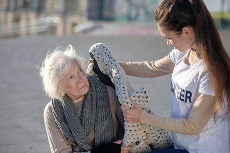 Bringing warm coat. Helpful volunteer bringing warm coat for homeless woman sitting alone outside
