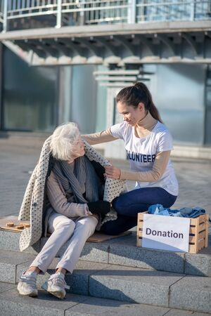 Clothing and donation. Dark-haired volunteer bringing some warm clothing and donation for homeless woman