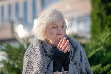 Pensioner feeling miserable. Blue-eyed homeless pensioner feeling miserable and hungry spending day outside Reklamní fotografie