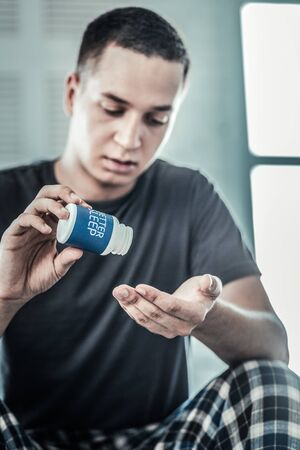 Sleeping pills. Selective focus of a bottle with pills being held by a sad young man
