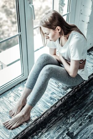 All alone. Unhappy pale woman sitting on the windowsill while feeling depressed Reklamní fotografie