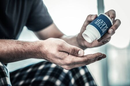 Sleeping medicine. Close up of a bottle with sleeping pills being put on a male palm Reklamní fotografie