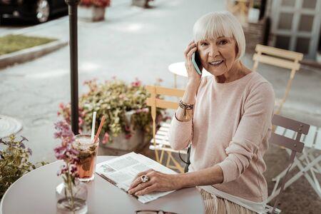 Mobile communication. Joyful elderly woman smiling while making a phone call