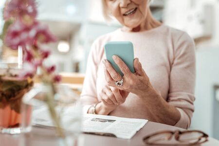 Digital device. Selective focus of a nice modern smartphone while being in hands of a nice elderly woman Stok Fotoğraf - 133949069