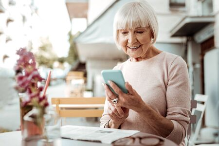 Digital technology. Delighted elderly woman using her new smartphone while sitting at the table Stok Fotoğraf