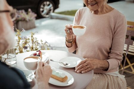 Delicious drink. Joyful aged woman drinking her tasty cappuccino while being in the cafe 스톡 콘텐츠 - 133949110