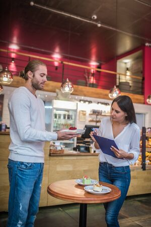 Having quality check. Couple wearing jeans looking at dessert while having quality check and composing menu