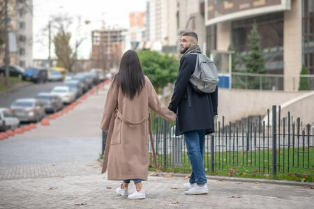 Young couple. Nice young people walking hand by hand while showing their feelings Stockfoto
