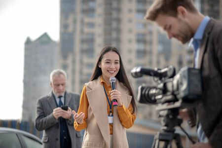 Live. Young cute female reporter in a beige outfit talking to a videocamera