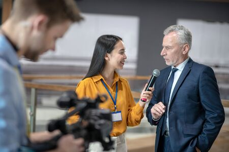 Some more information. Asian female reporter holding a microphone in her hand while talking to a businessman