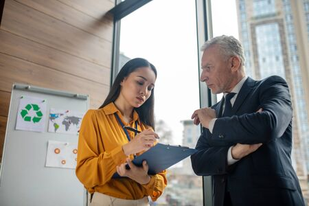 Assistant. Young asian business woman with long hair making notes while her boss talking
