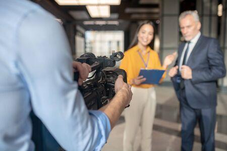 Feeling satisfied. Asian female reporter wearing beige pants smiling nicely
