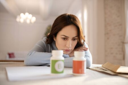 Better vitamins. Young cute woman in grey homewesar choosing vitamins