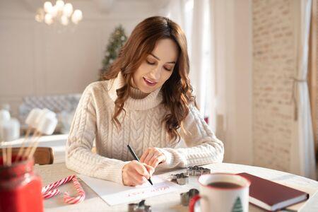 Good mood. Beautiful long-haired woman writing a wish list at christmas