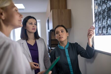 Brains scan. Three female doctors looing serious discussing mri brains scan Imagens