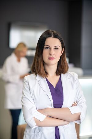 At work . Beautiful dark-haired doctor wearing white robe looking confident Stok Fotoğraf
