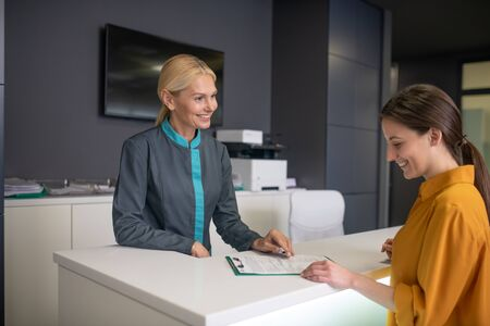 New visitor. Blond receptionist in clinic talking to a visitor