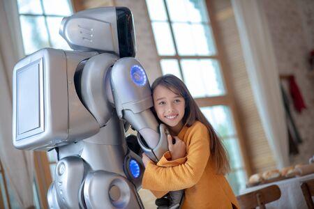 Human dn robot. Cute girl feeling good with her robot friend hugging him