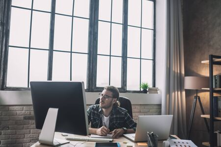 Web designer. Young bearded man in eyeglasses looking at the monitor