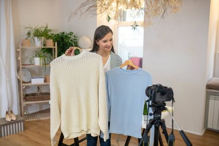 Fashion blogger. Good looking young woman standing in front of the camera while giving advice about clothes