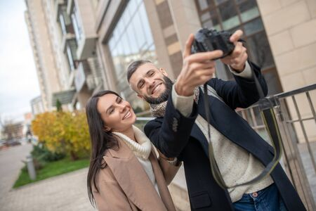 Memorable moments. Nice married couple standing together while taking a photo of themselves