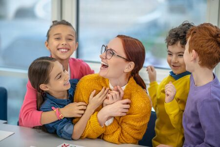 Good relations with the teacher. Happy pupils hugging their favourite teacher Фото со стока