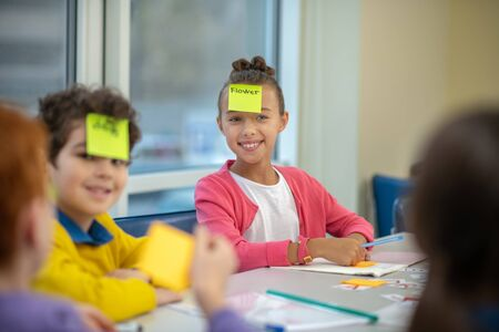 Helpful lesson. Cheerful children sitting at the desk wearing different words on their faces during the vocabulary learning