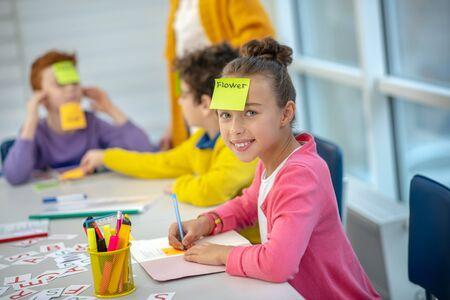 Disfrutando del juego. Niña de la escuela alegre sentada frente a sus compañeros de clase con pegatinas de colores en sus caras