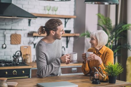Peaceful morning. Grey-haired mom and her son sitting in the kitchen Stock Photo - 137175743