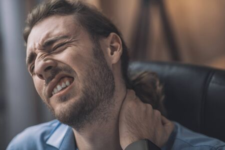 Painful feeling. Young bearded man in blue shirt suffering from aching neck