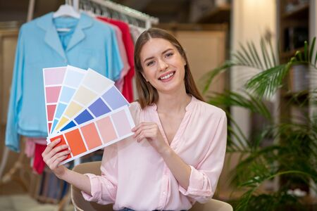 Color scales in the work of the designer. Beautiful smiling designer girl with color scales in her hands, sitting in a chair in front of a clothes rack.