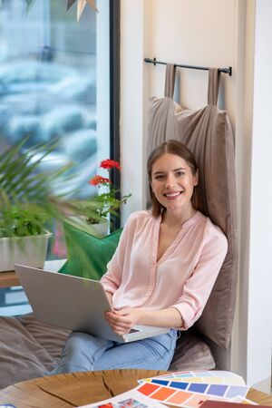 Working atmosphere. A smiling young designer working with her laptop