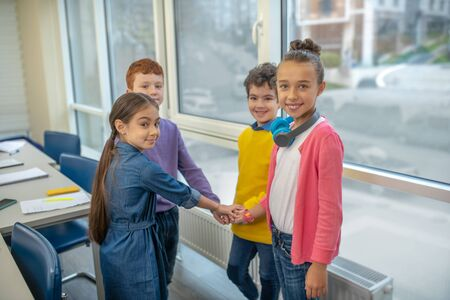 Forming a group. Elementary classmates holding their hands standing behind the desks in the classroom