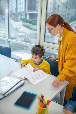 Individual approach to pupils. Teacher working with the schoolboy individually 스톡 콘텐츠
