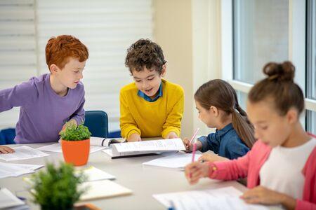 Clase de aprendizaje. Dos niñas de la escuela y dos niños sentados en un escritorio y escribiendo