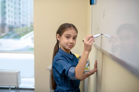 Using the whiteboard in class. Girl writing on the whiteboard with marker