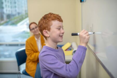 Good pupil. A smiling red-haired boy writing symbols on the whiteboard