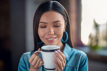 Arôme merveilleux. Heureuse belle femme fermant les yeux en sentant le café