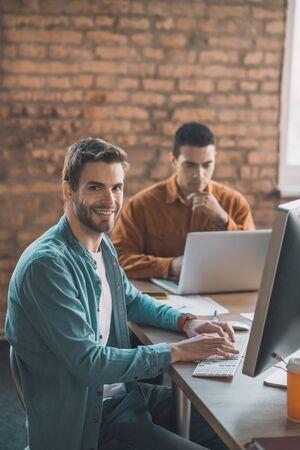 En el trabajo. Hombre inteligente alegre sentado frente a su computadora mientras está en el trabajo