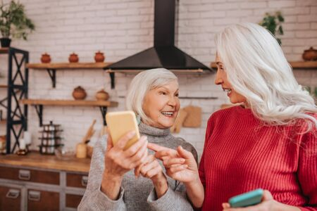 Staying up to date. Two mature grey-haired positive ladies talking about new technologies