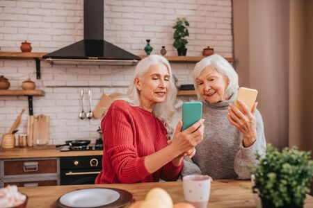 New apps. Two mature grey-haired positive ladies looking great Foto de archivo
