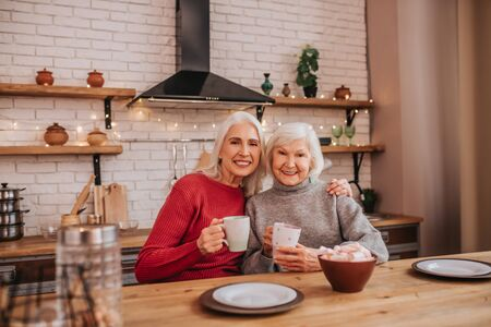 Breakfast time. Two mature grey-haired positive ladies having breakfast Stock fotó