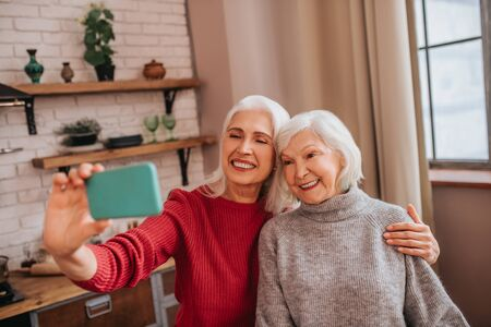 We are the best. Two mature grey-haired positive ladies looking proud Foto de archivo