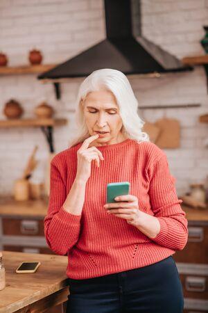 Cómo usarlo. Hermosa anciana en blusa roja mirando desconcertado