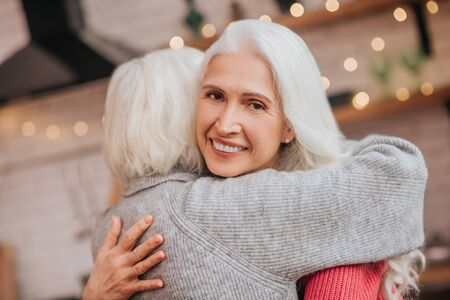 Happy people. Two mature grey-haired positive ladies looking happy