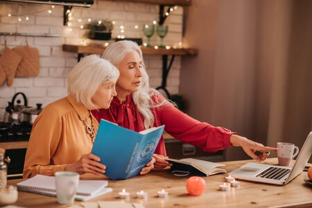 Read this. Two grey-haired pleasant cute ladies looking amused while studying together Foto de archivo