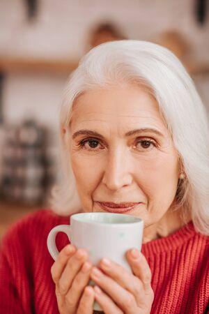 Morning tea. Beautiful elderly woman in red blouse enjoying her tea