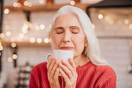 Wonderful tea. Beautiful elderly woman in red blouse smelling her tea