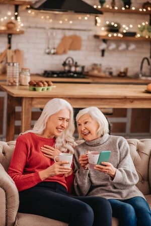 Enjoying the day. Two grey-haired pleasant cute ladies sitting on the sofa and smiling Foto de archivo
